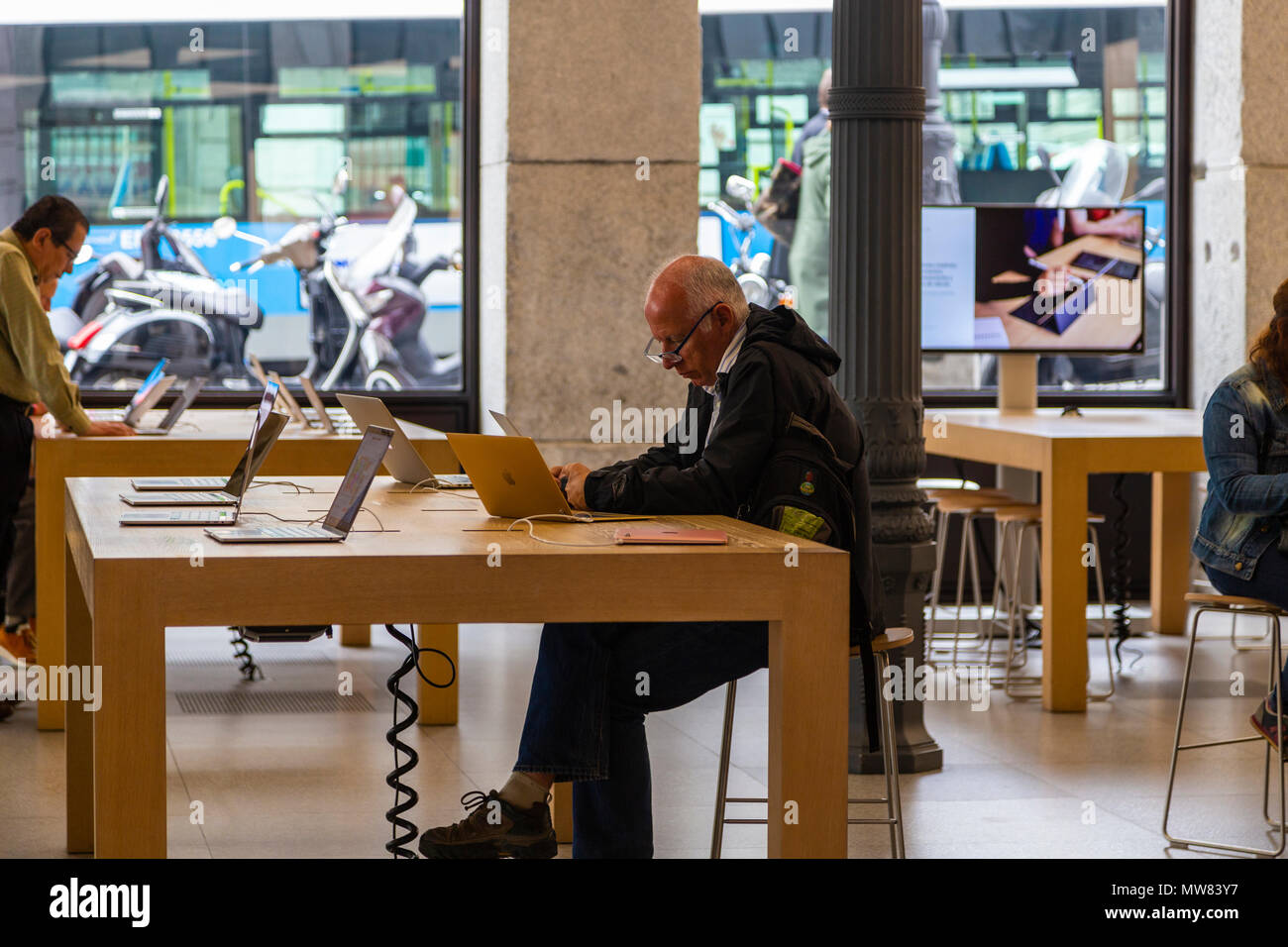 Old man using Mac on the Apple Store of Madrid, Spain Stock Photo