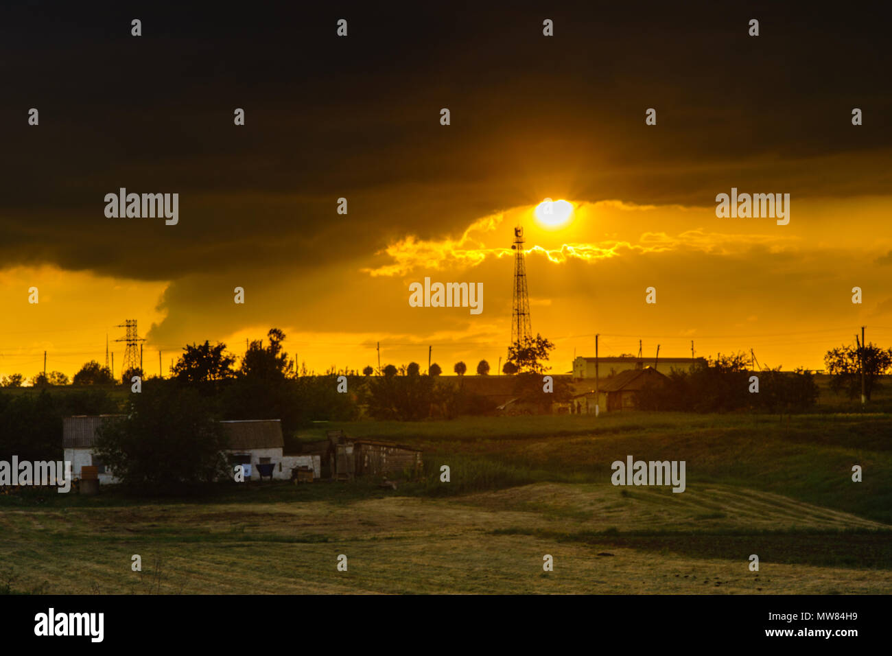 sunset over the field with houses in the village - Stock Image