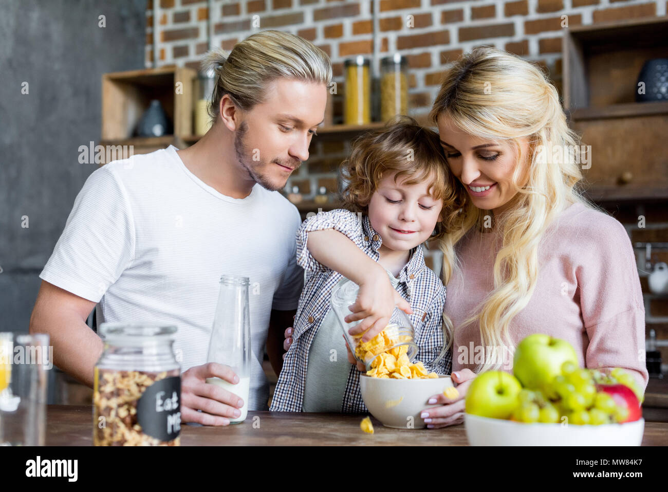 happy young family eating corn flakes for breakfast at home - Stock Image