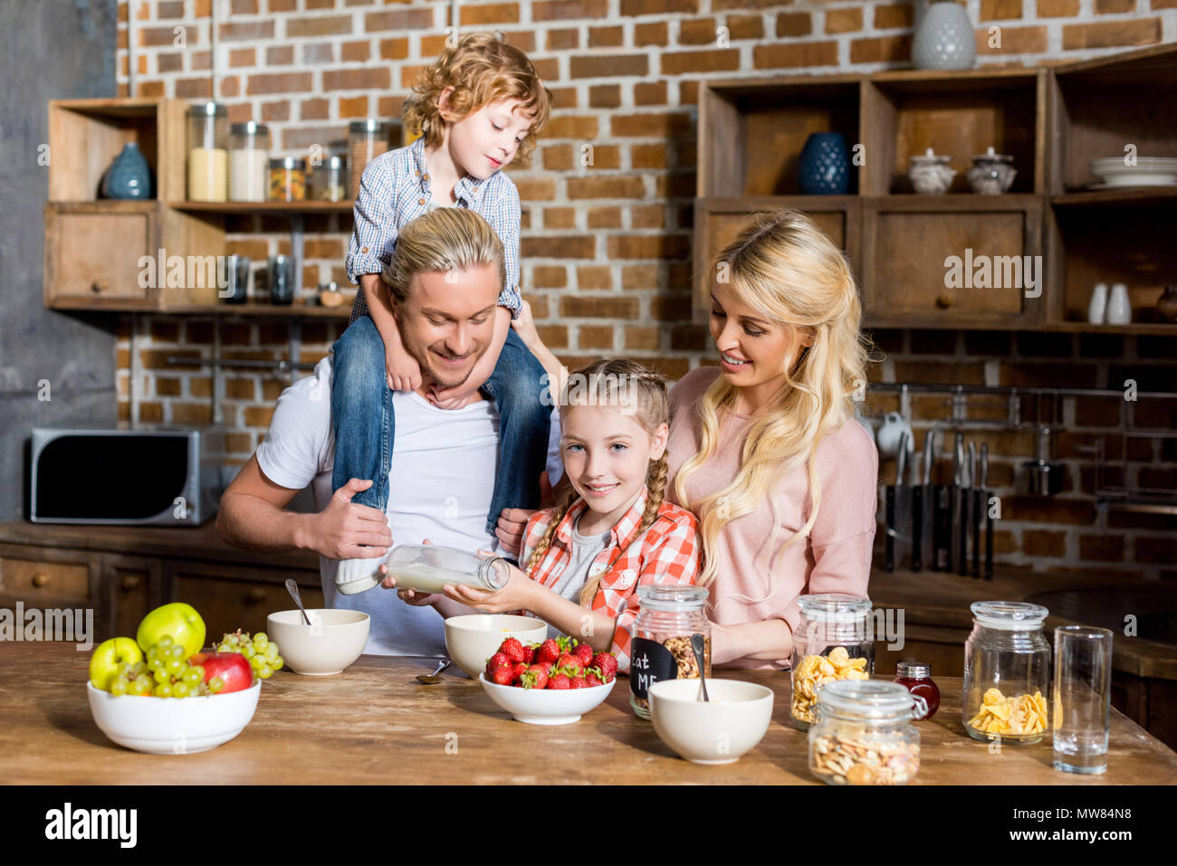 happy family with two children preparing and eating breakfast together at home - Stock Image