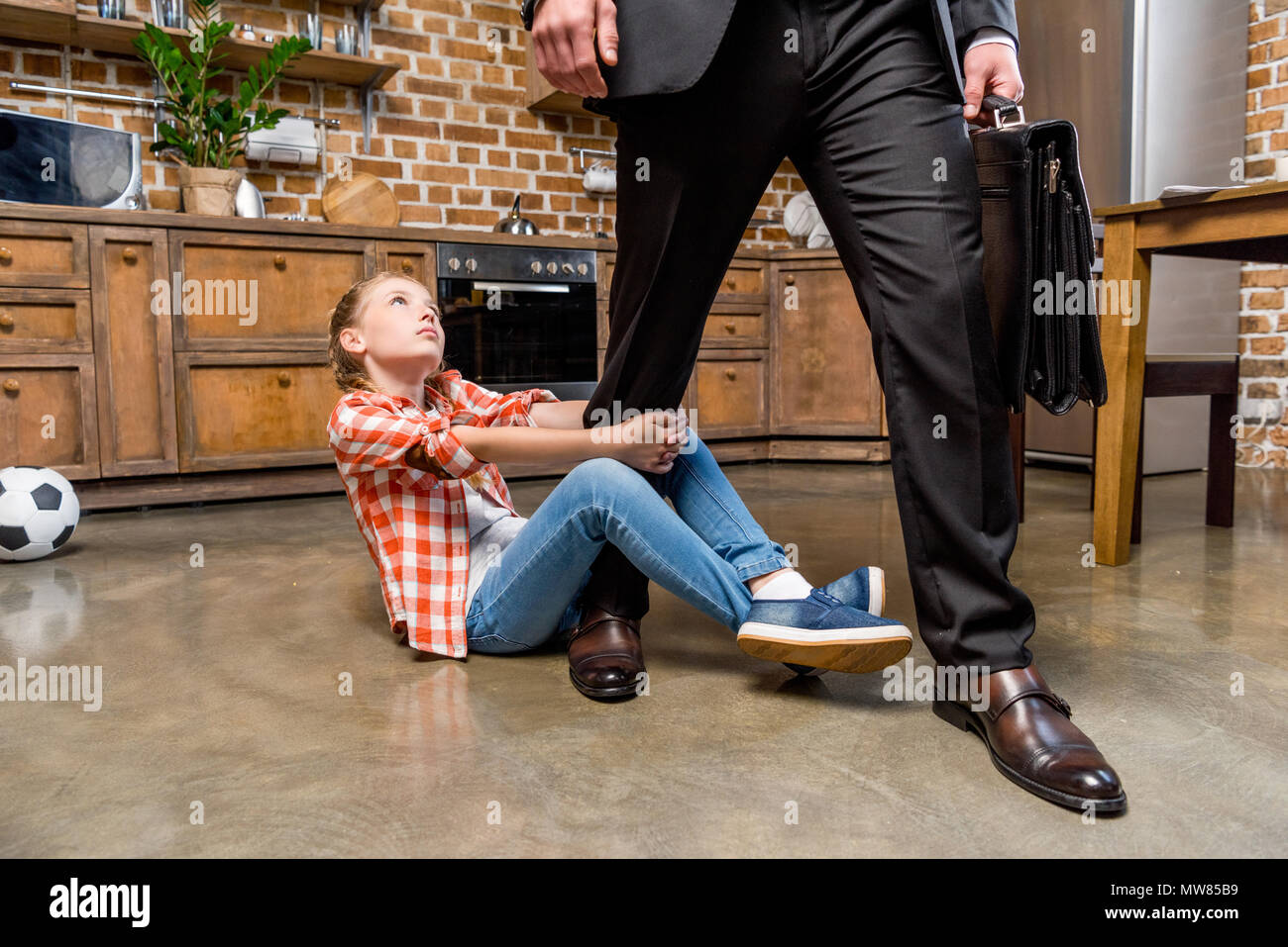 cropped shot of upset little girl hugging leg of busy father not letting him go - Stock Image