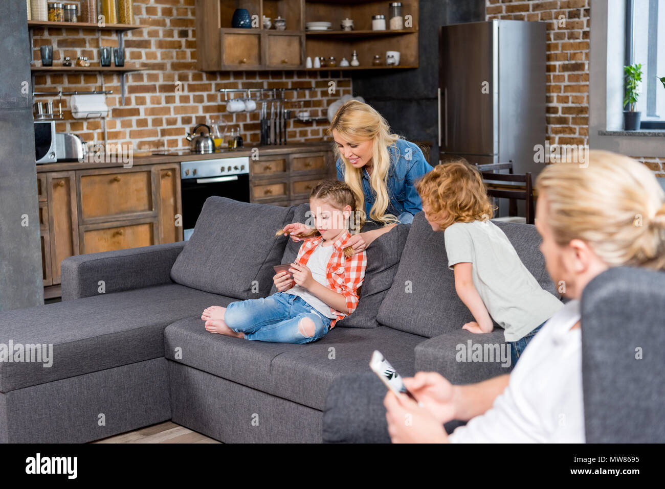 parents with two little kids spending time at home - Stock Image