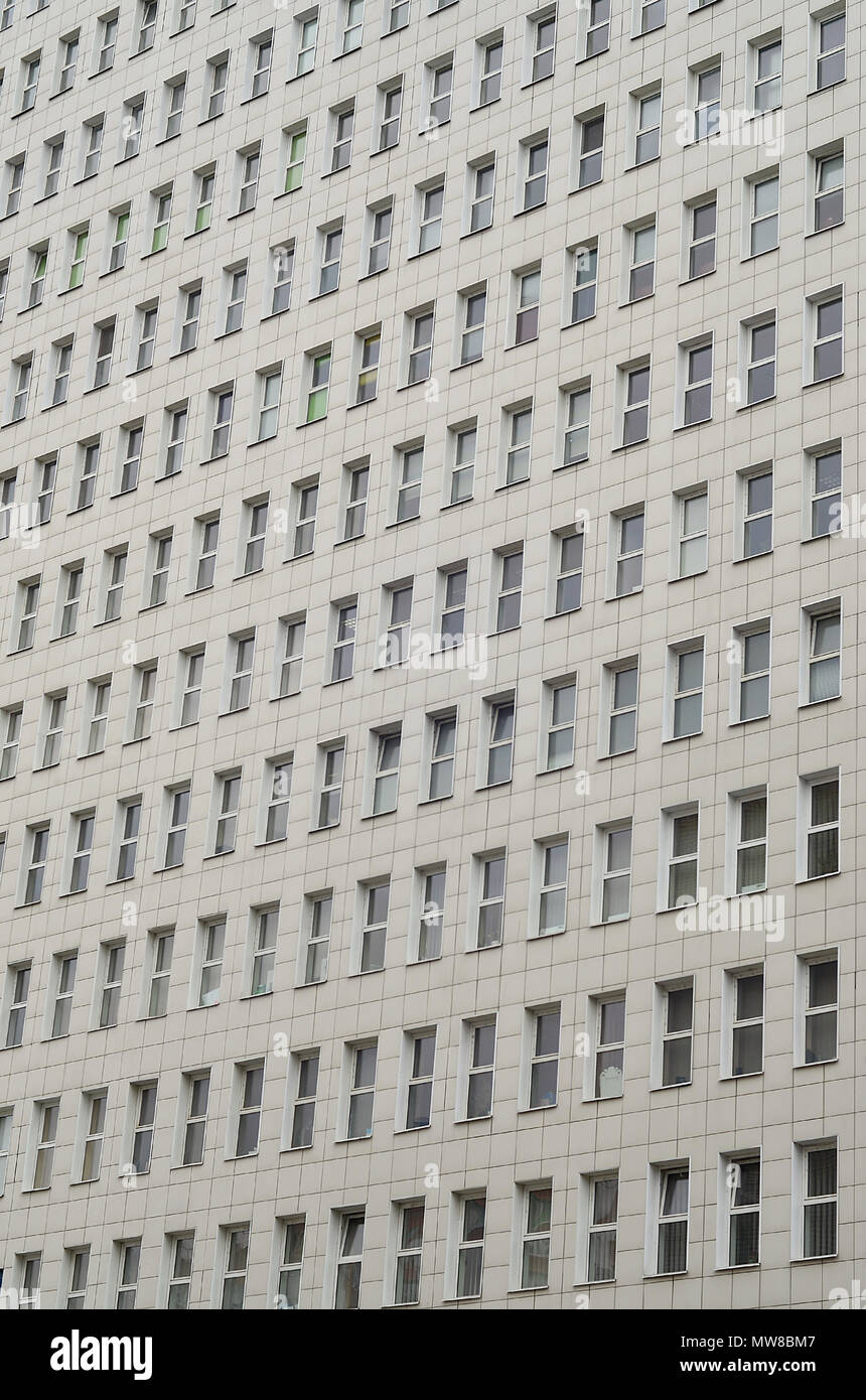 A pattern of many windows from a multi-storey office building. A large number of plastic windows in the wall of a modern multi-storey building Stock Photo