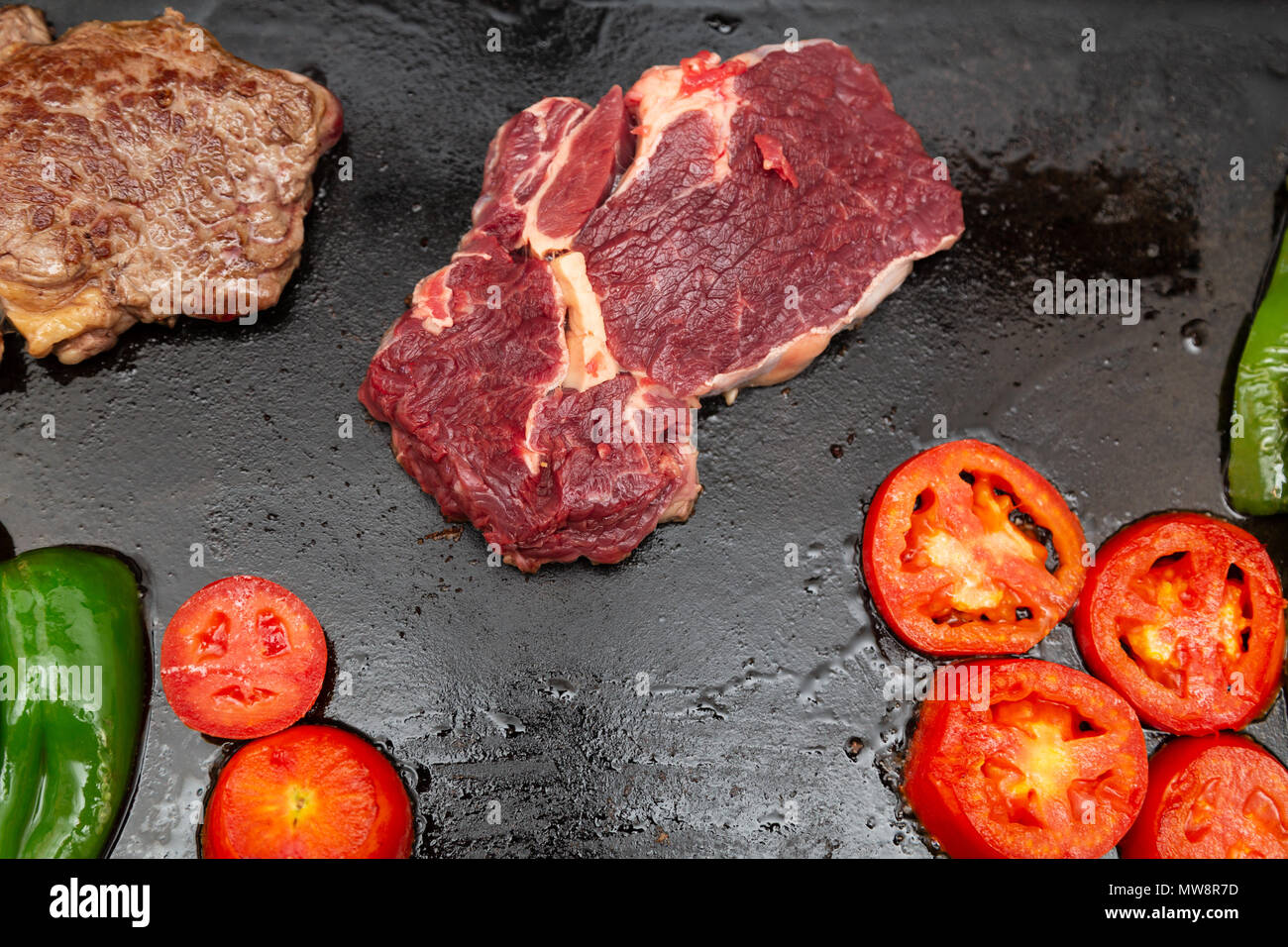 Rib eye steak (Spanish: Bife ancho) raw and grilled, tomatoes and green peppers on a cast iron rectangle griddle plate, flat lay - Stock Image