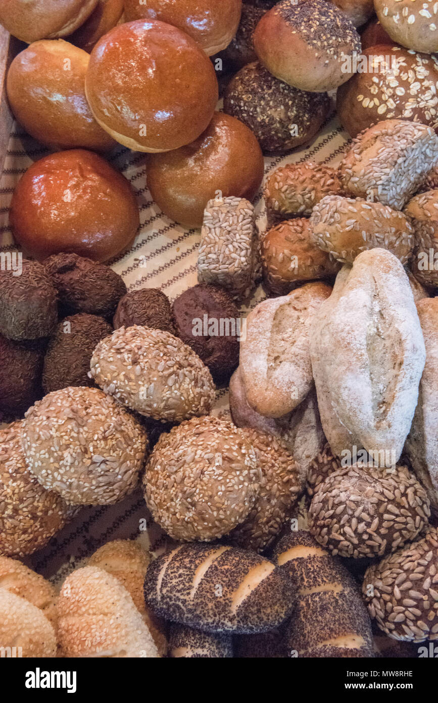fresh breads and baked products at an artisan baker s stall at borough market in london. loaves of bread and rye bread rolls and baguettes on sale eat - Stock Image