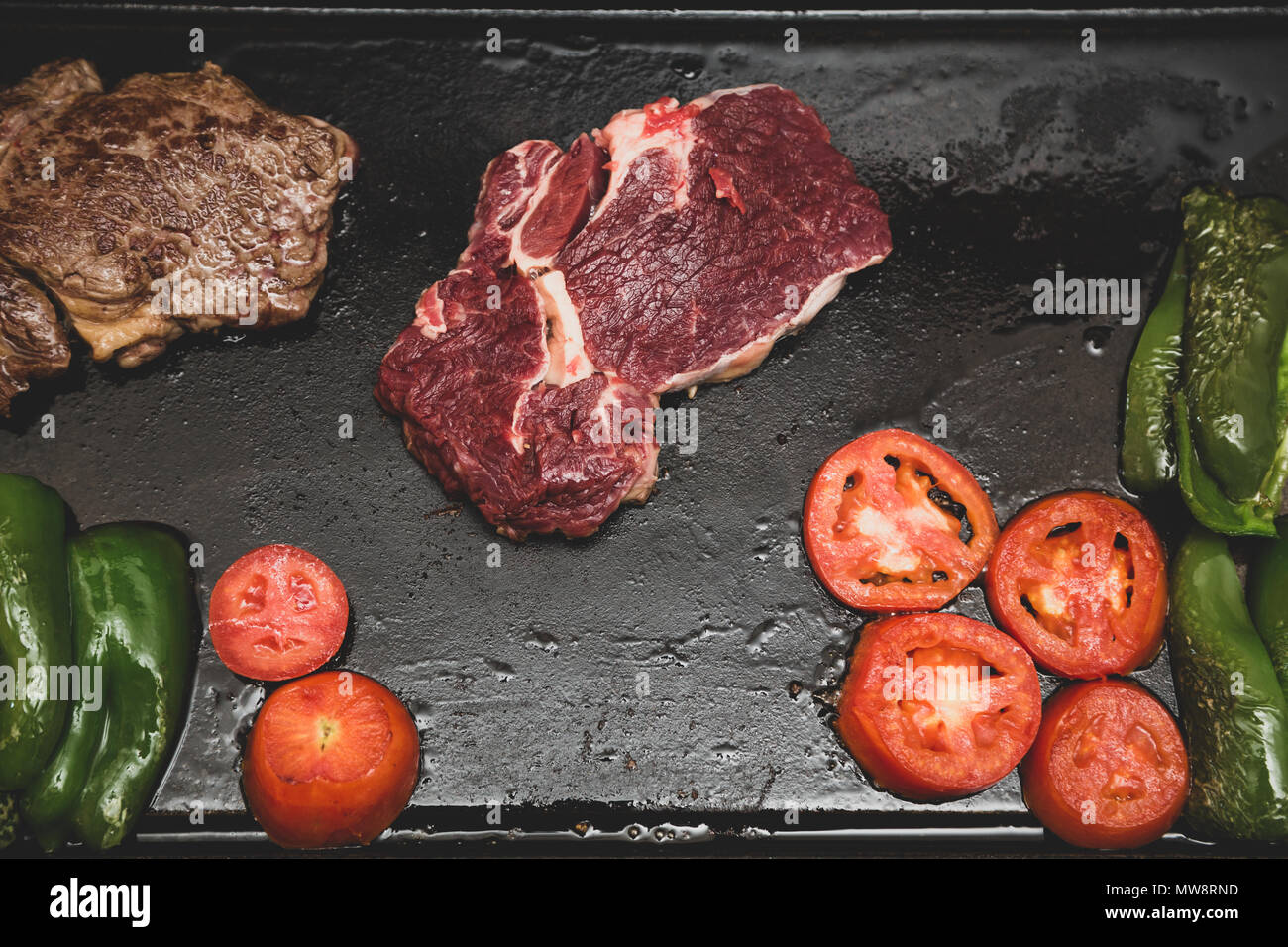Rib eye steak (Spanish: Bife ancho) raw and grilled, tomatoes and green peppers on a cast iron rectangle griddle plate, vintage toned, flat lay - Stock Image