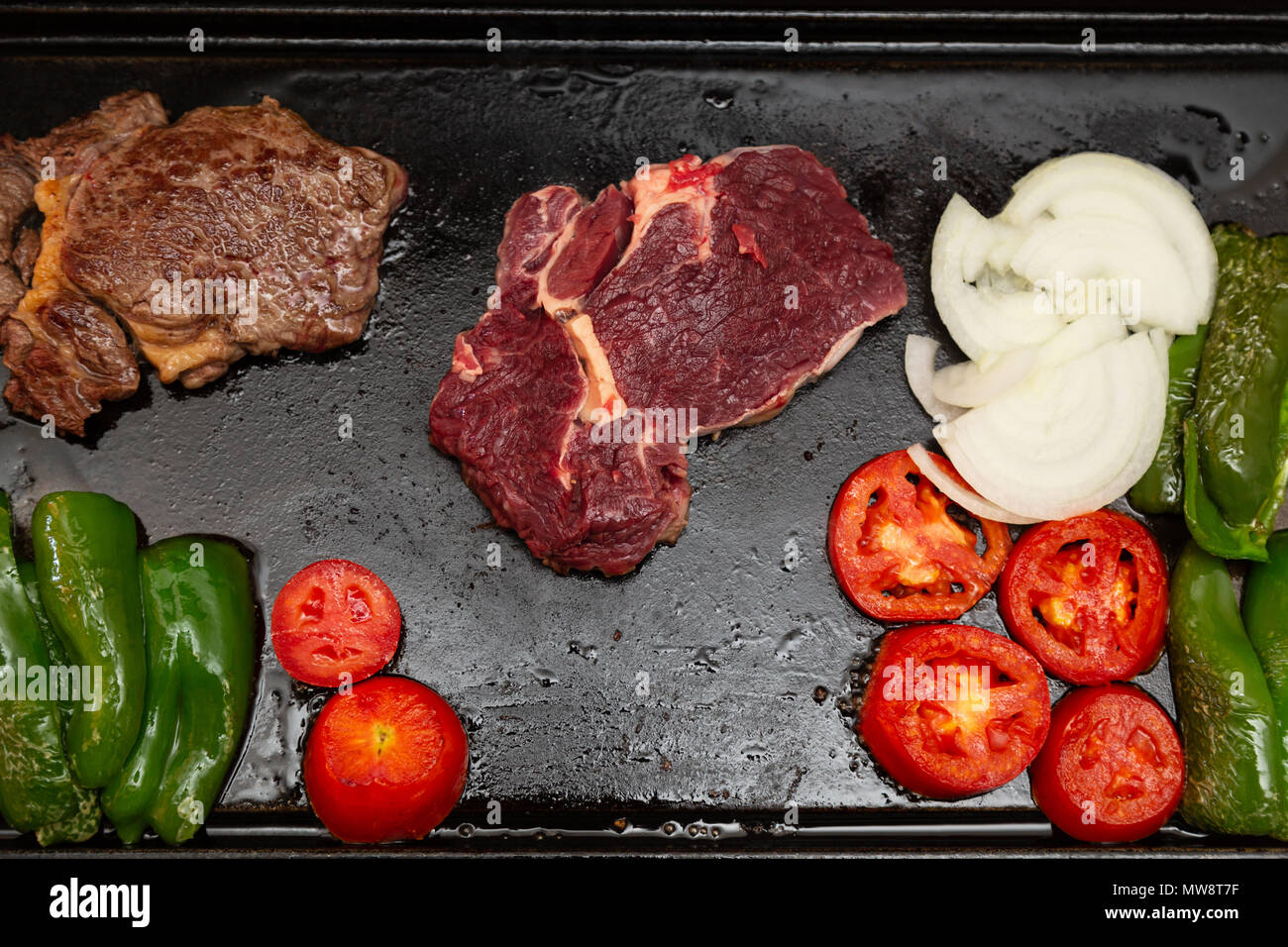 Rib eye steak (Spanish: Bife ancho) raw and grilled, onions, tomatoes and green peppers on a cast iron rectangle griddle plate, flat lay - Stock Image