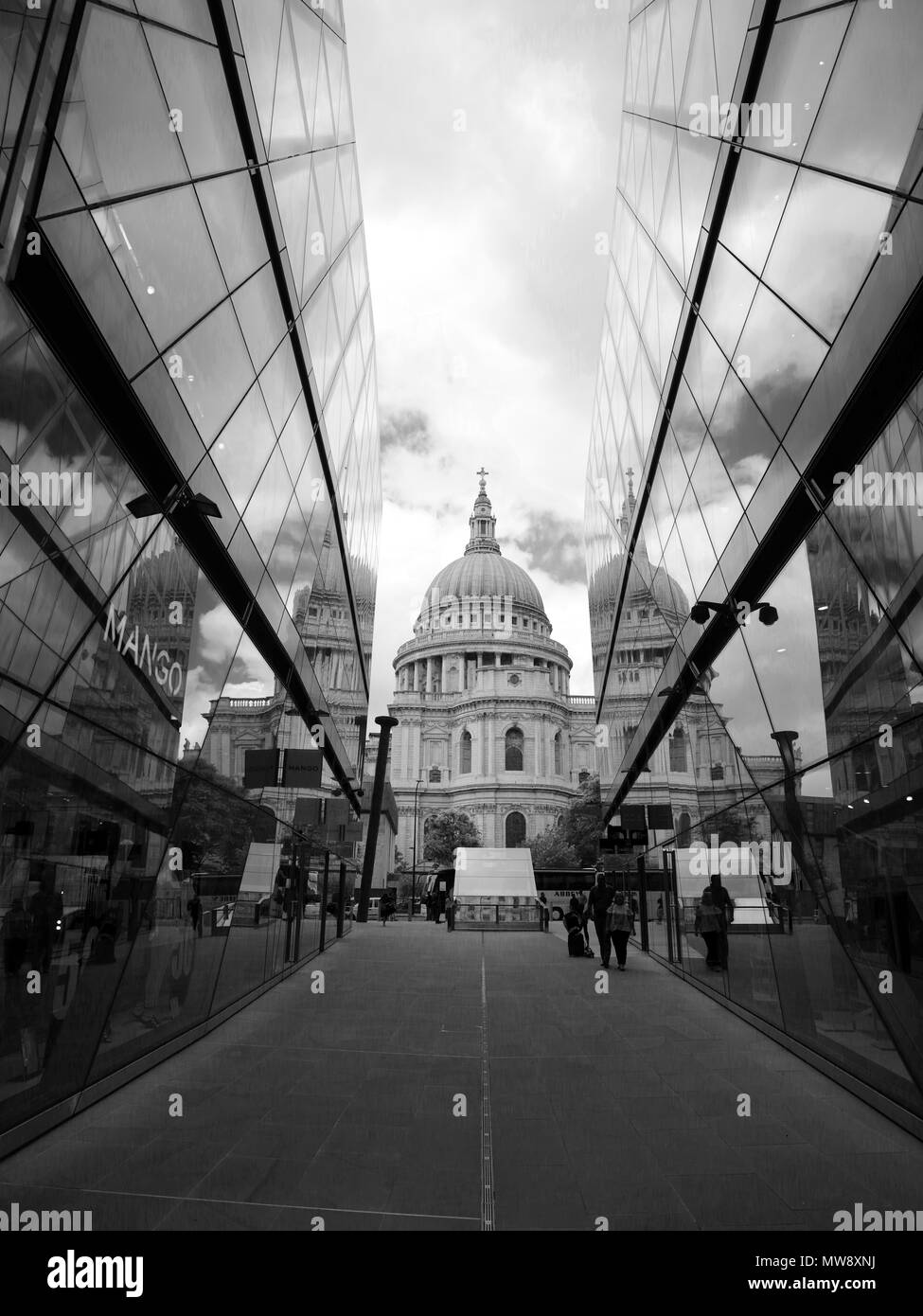 Black and white view of St Paul's Cathedral, viewed from between two glass buildings, showing the reflection of St Paul's in the glass buildings. Stock Photo