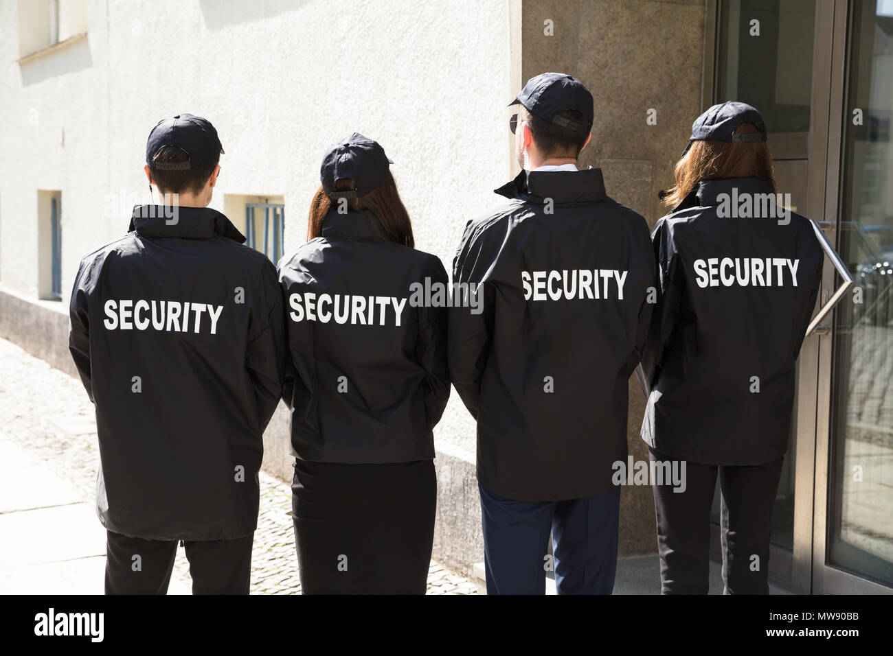 Rear View Of Security Guards Wearing Uniform Standing In A Row - Stock Image