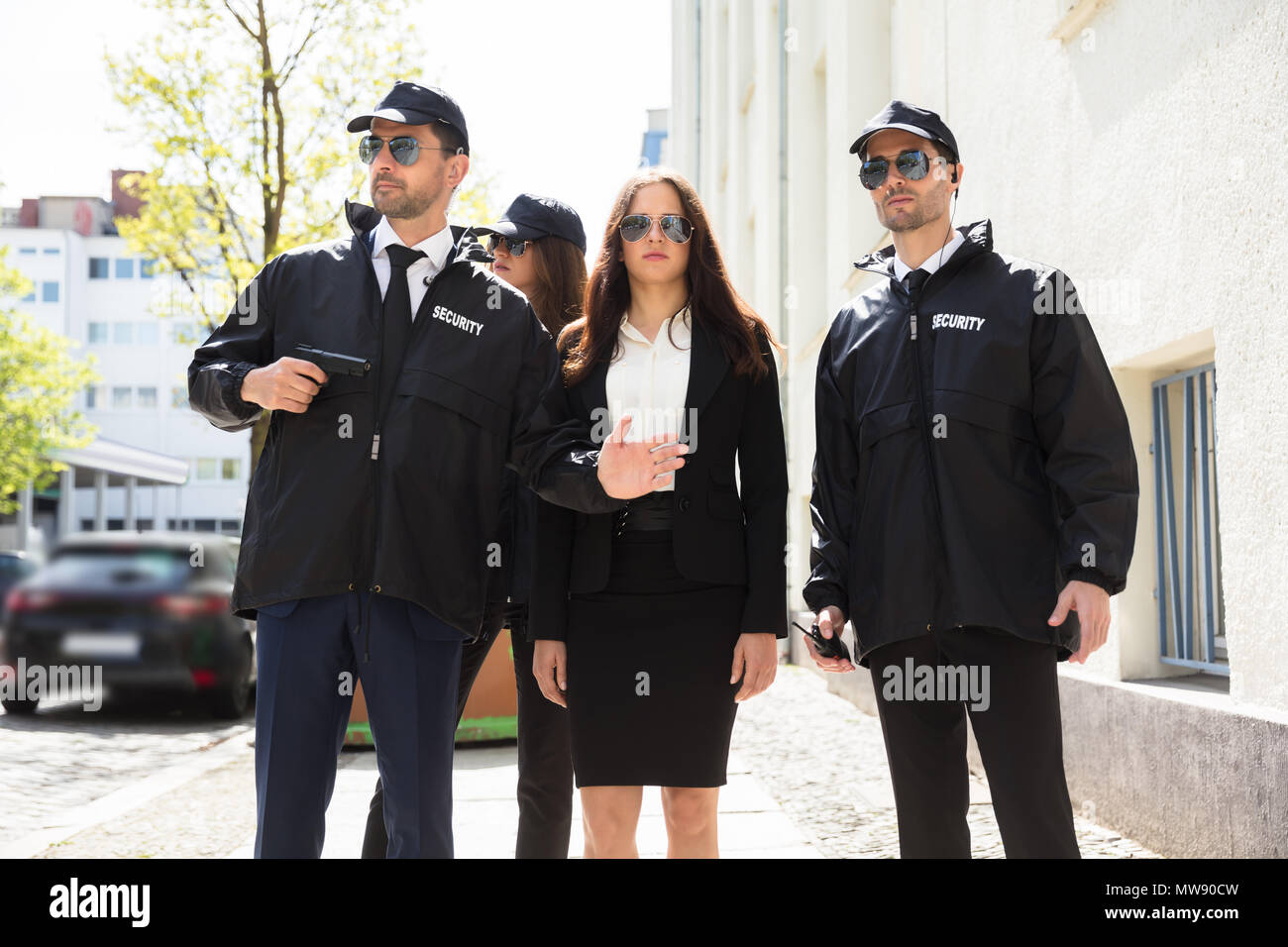 Portrait Of Beautiful Young Businesswoman With Bodyguards Standing On Sidewalk - Stock Image