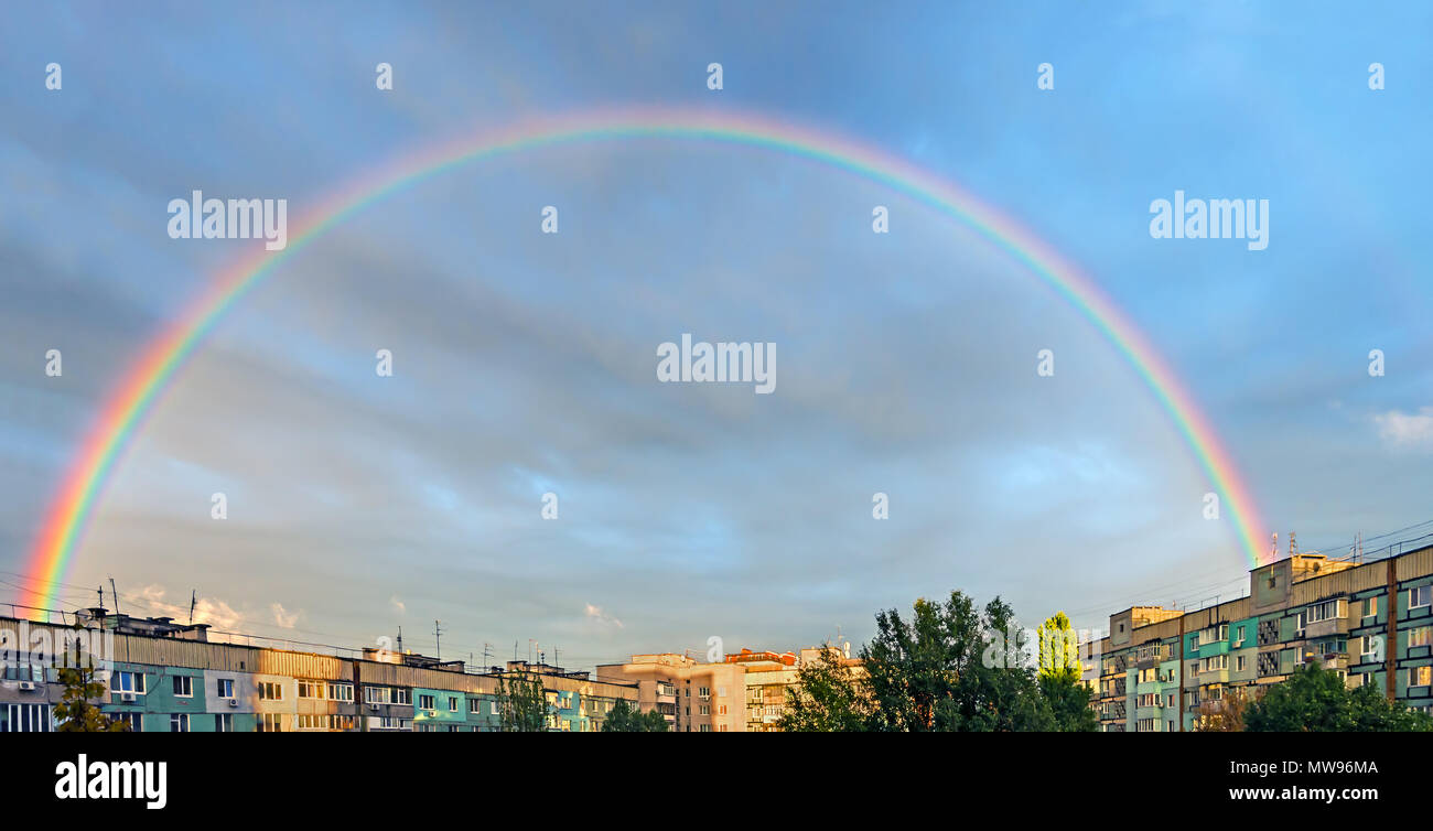 Pre-rain weather with a bright rainbow over the residential area of city - Stock Image