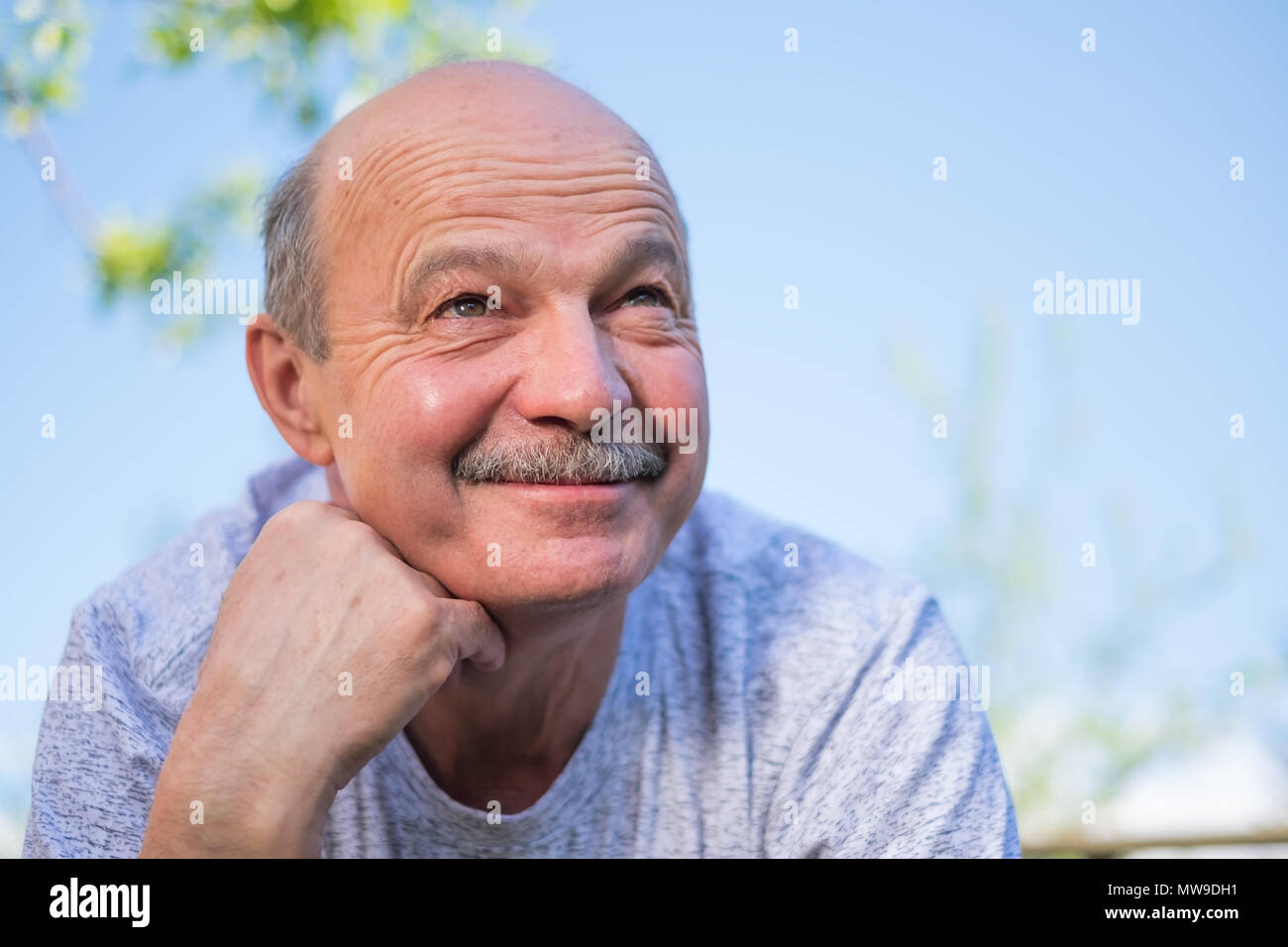 A man resting outdoor on sunny summer day. - Stock Image