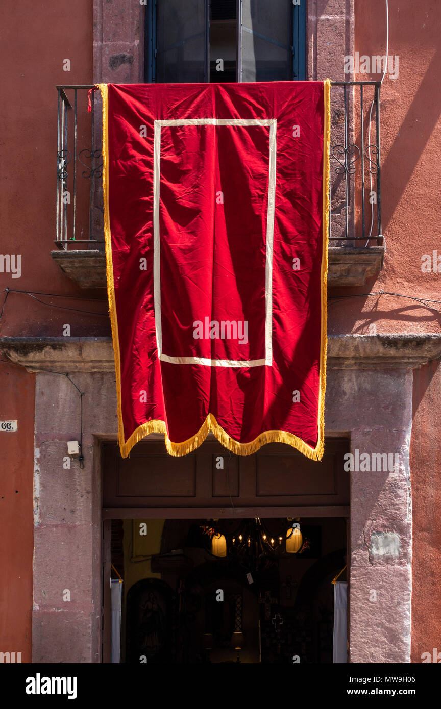 Red and gold banner dropped from balcony in honer of the Feast of Corpus Christi in San Miguel de Allende, Mexico - Stock Image