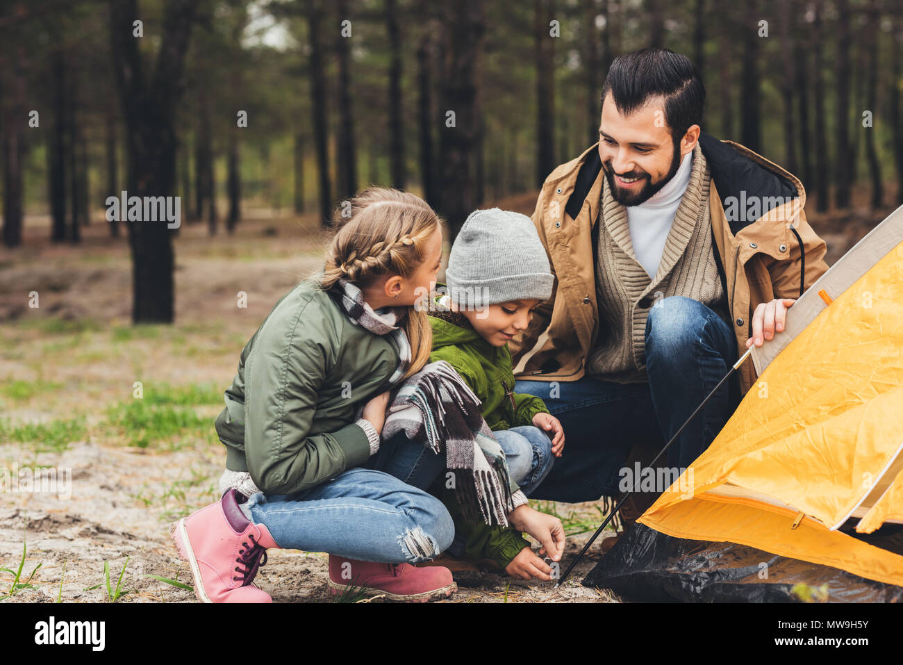 happy young father and kids installing camping tent in pine forest - Stock Image