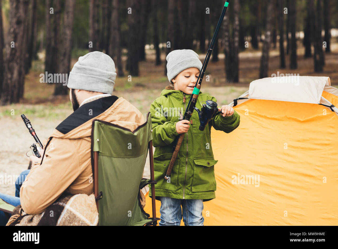 father and son with fishing rods spending time together on trip - Stock Image