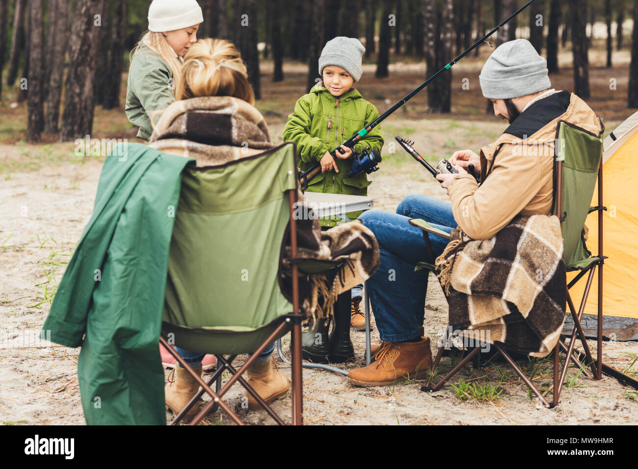 family with fishing rods on camping trip - Stock Image