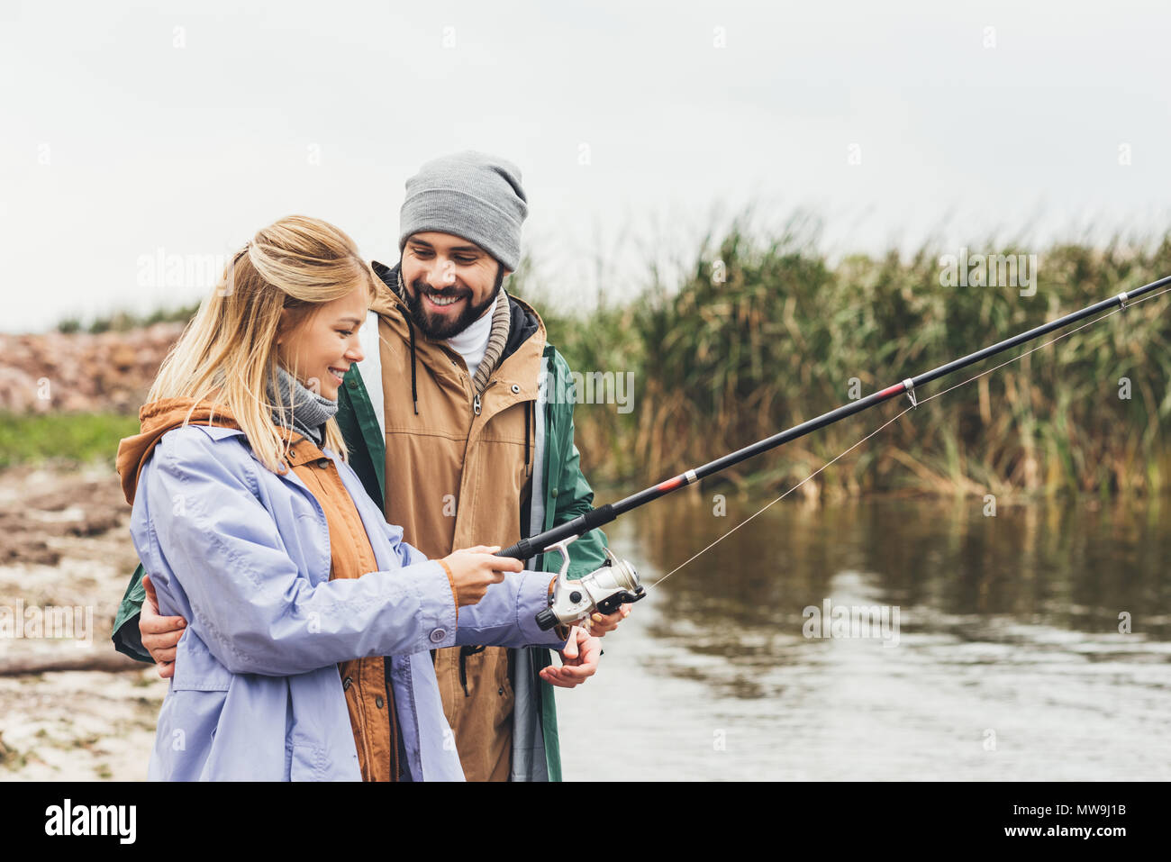 beautiful couple fishing together on cloudy day - Stock Image