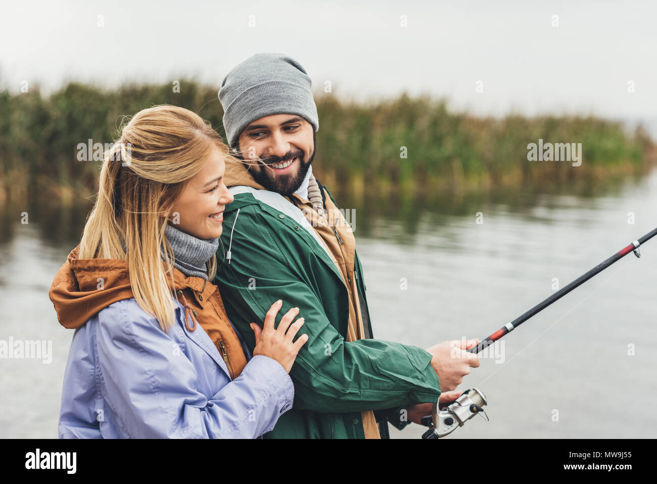 happy young couple embracing while fishing together - Stock Image