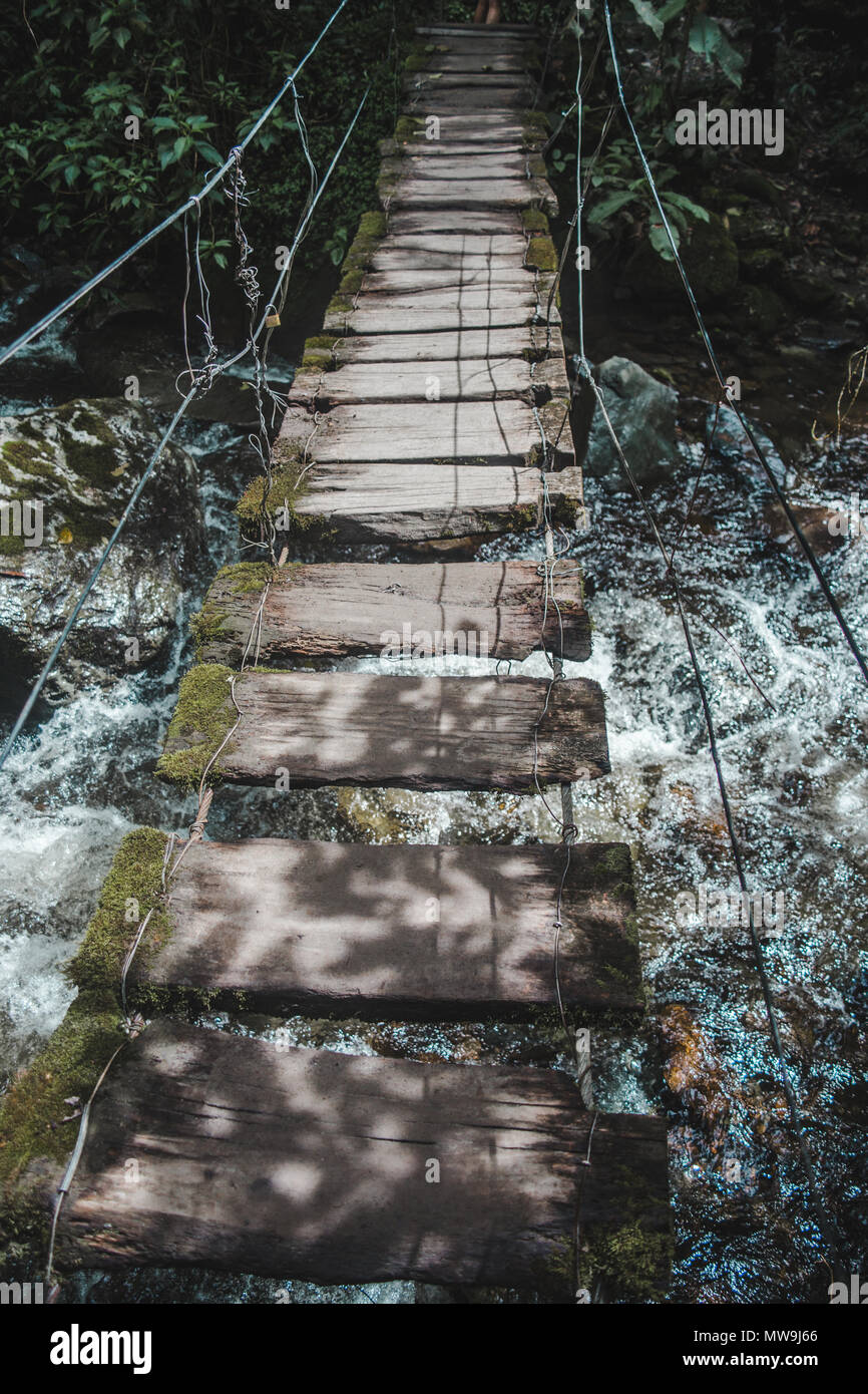Rickety rope and wood bridge going across a rocky river on a hiking trail in the Colcora Valley, Colombia - Stock Image