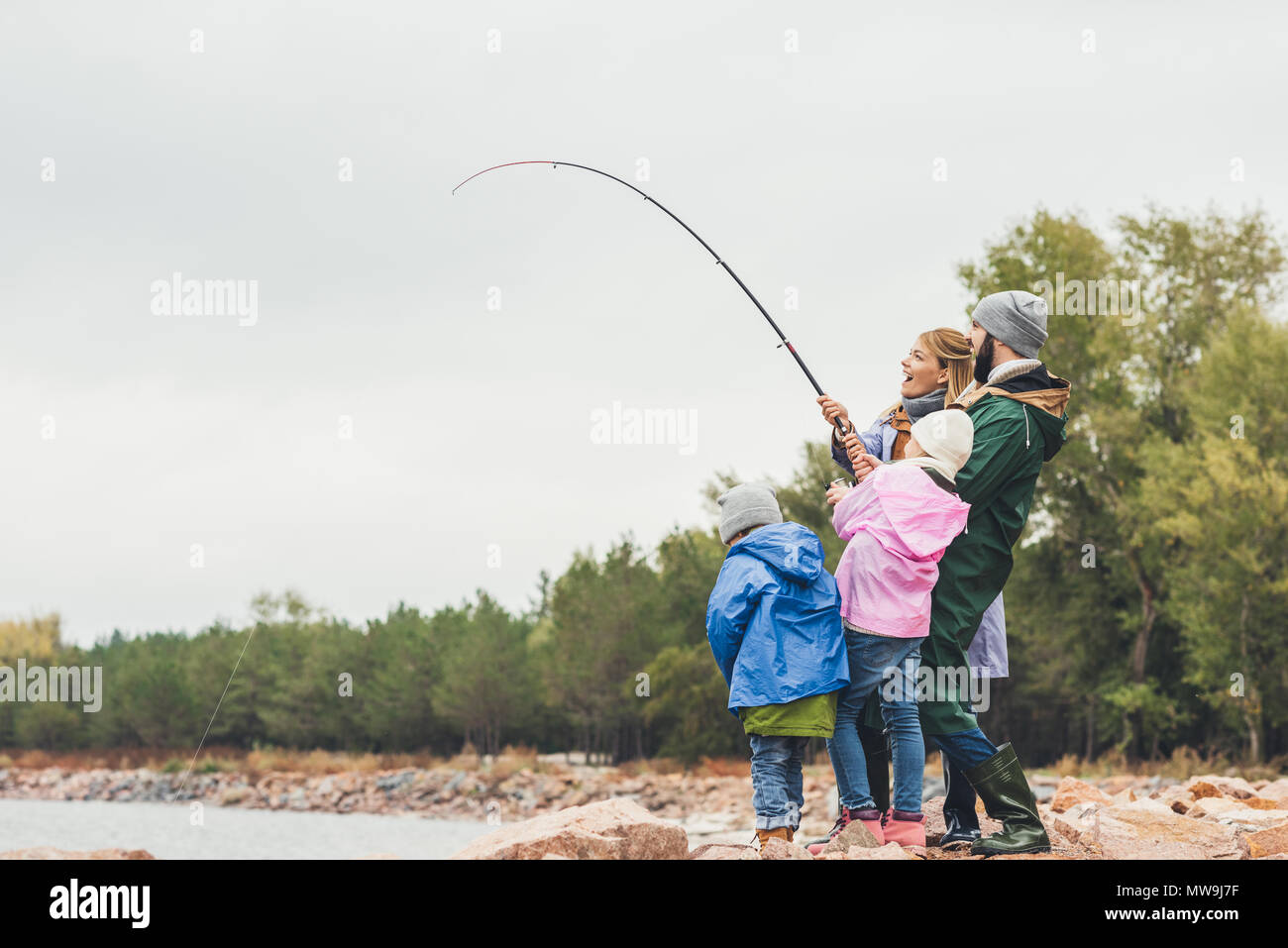 side view of young family fishing together - Stock Image