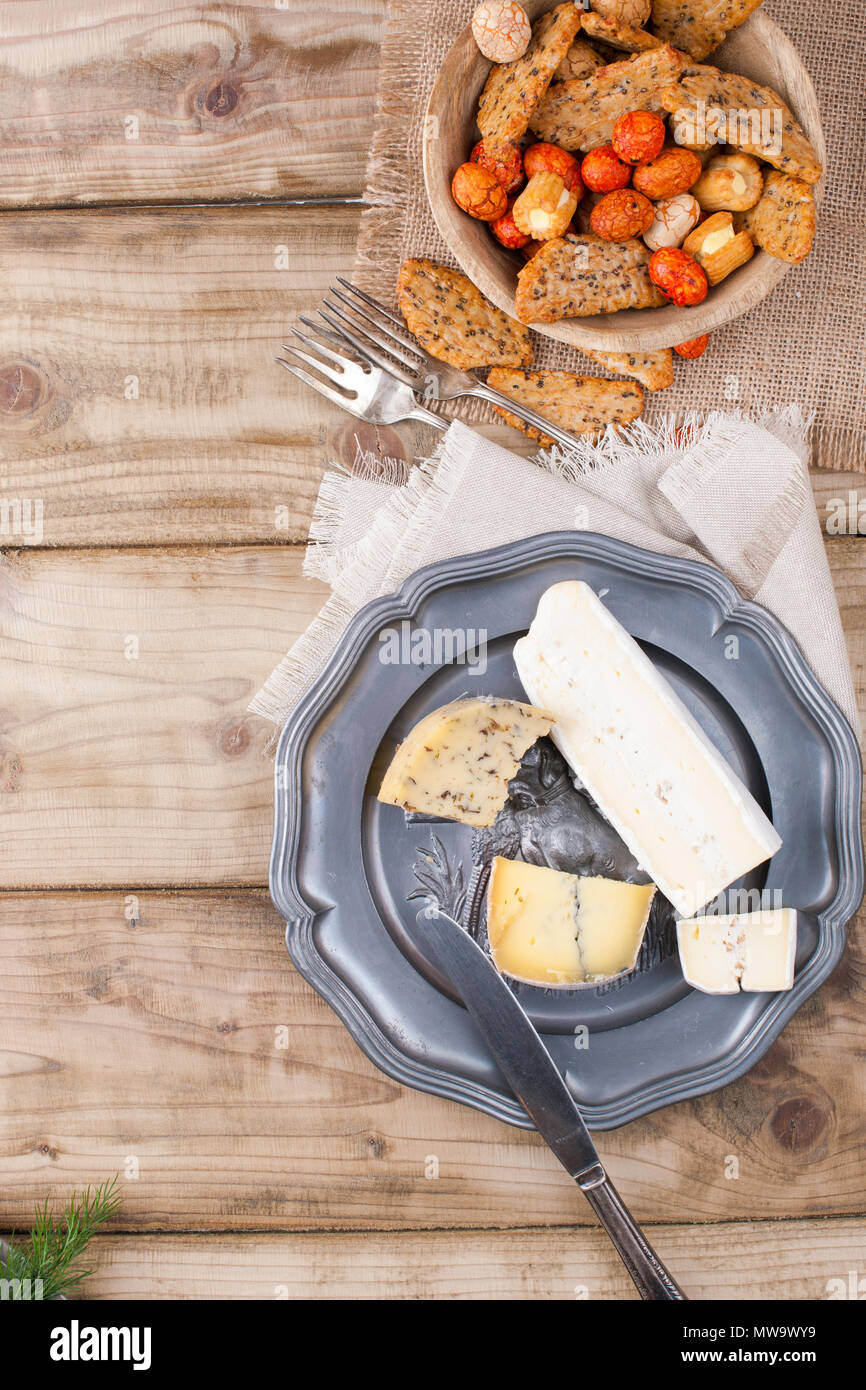 Snack on the plate and different cheese for the party. Vintage photo. Wooden background. Copy space. - Stock Image