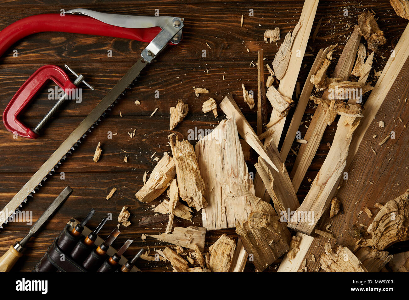 top view of chisels and coping saw with wooden pieces on table Stock Photo