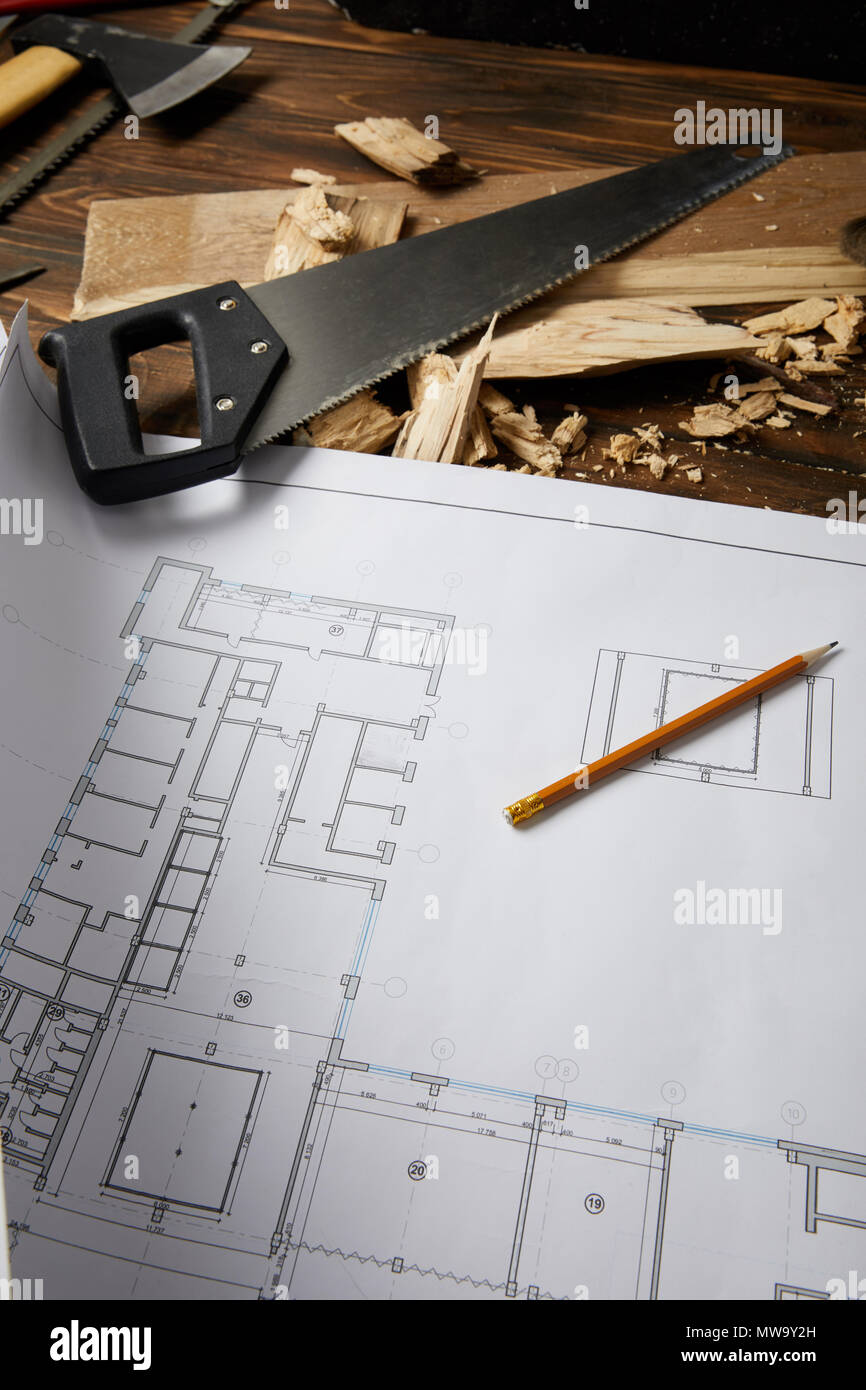 closeup view of architectural blueprint, pencil, handsaw, axe and coping saw on wooden table Stock Photo