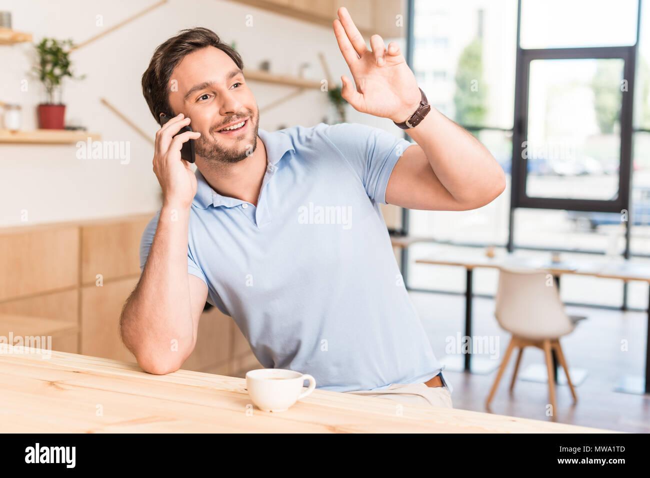 man calling for waiter or bartender in restaurant at bar counter - Stock Image