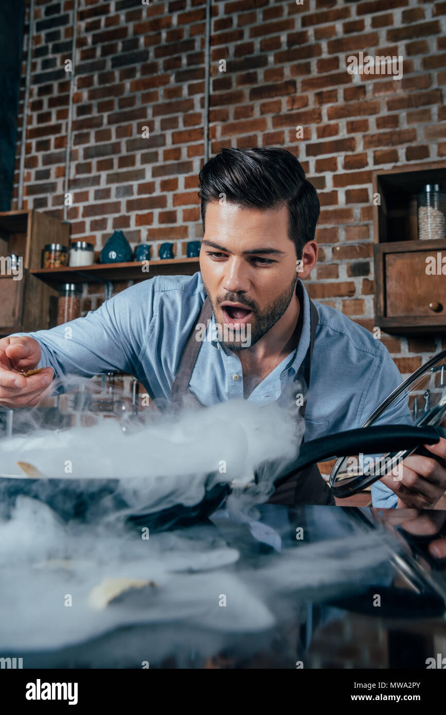 excited young man with apron cooking - Stock Image