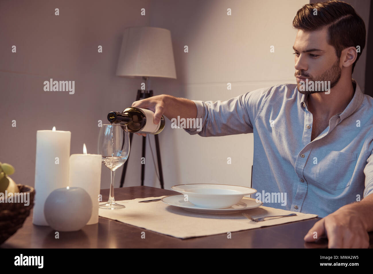 mna pouring wine in glass for romantic dinner - Stock Image