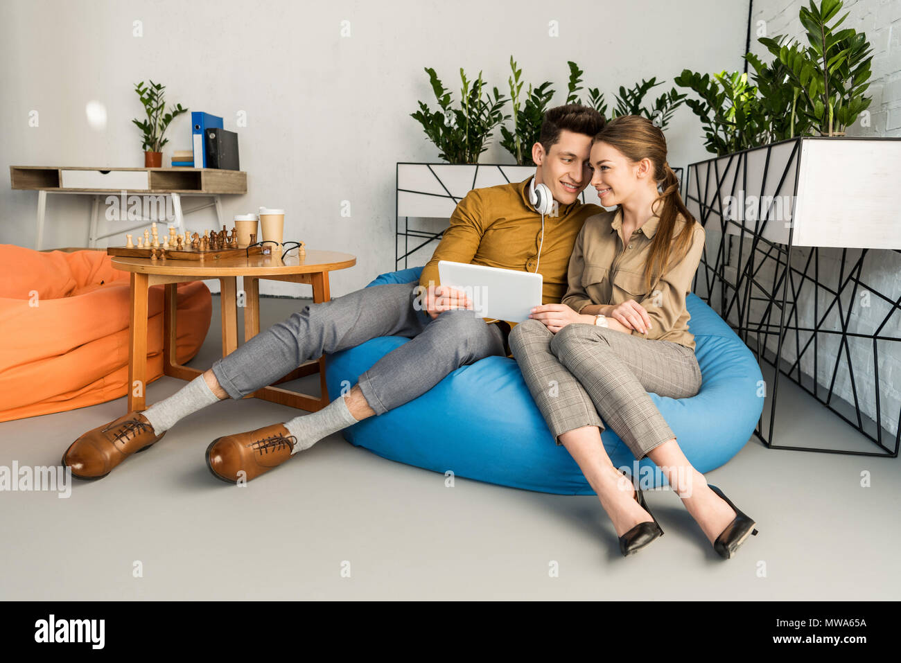 young couple cuddling using tablet together while sitting in bean bag - Stock Image