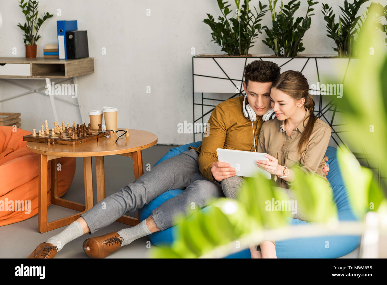young couple embracing using tablet together while sitting in bean bag - Stock Image