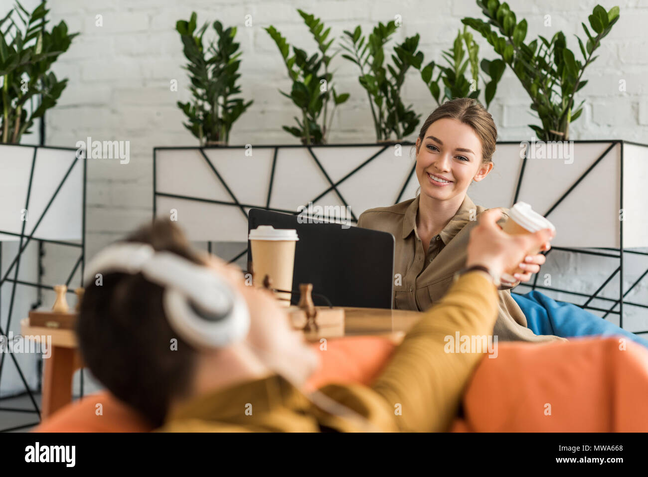 young man and woman drinking coffee and using devices while sitting in bean bags - Stock Image