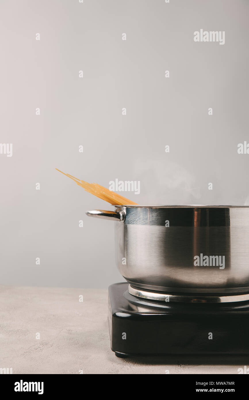 delicious spaghetti boiling in stewpot on concrete tabletop - Stock Image