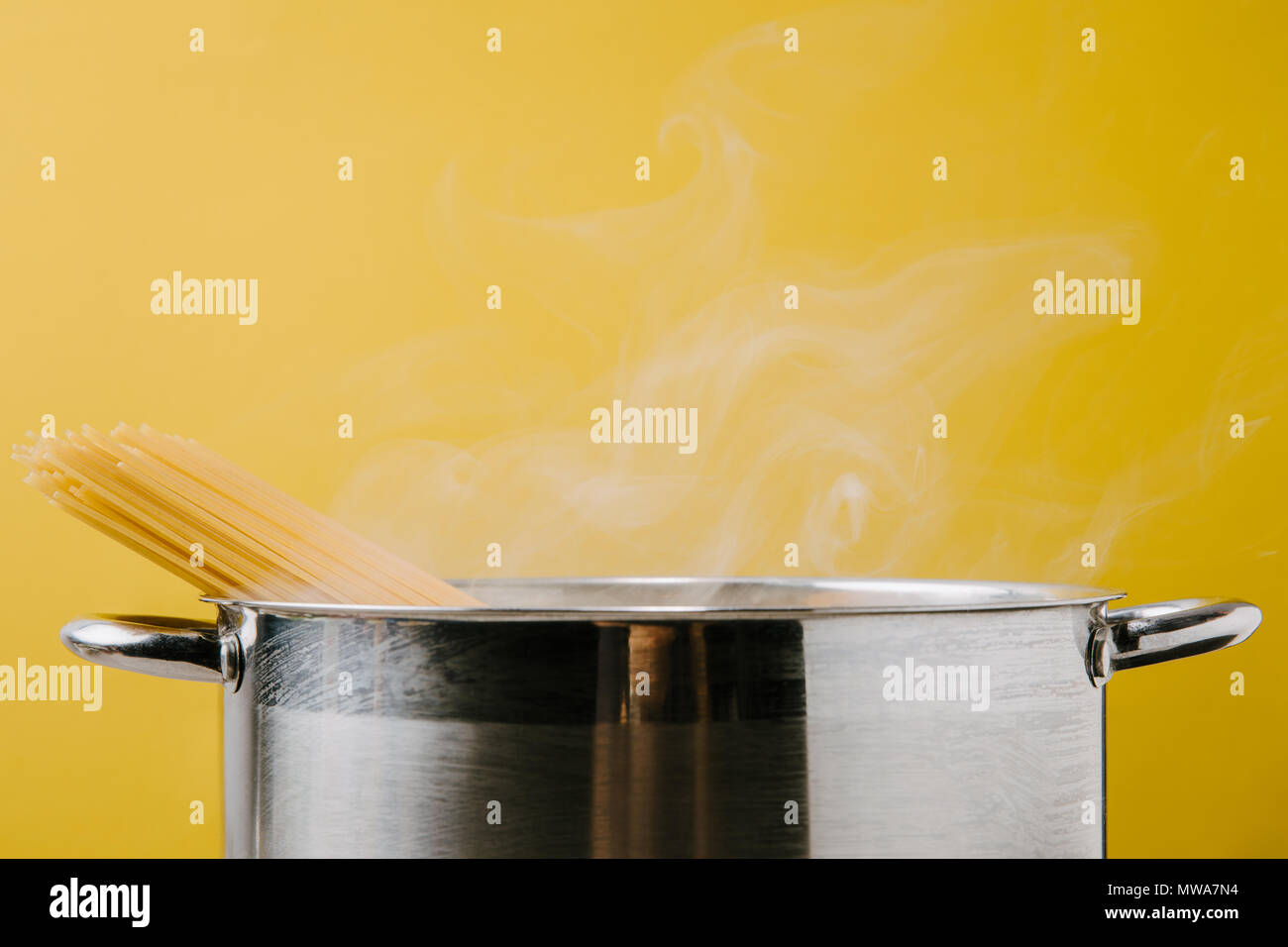 delicious spaghetti boiling in stewpot isolated on yellow - Stock Image