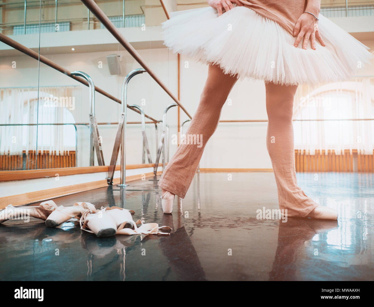 Ballerina in ballet pointe and white tutu stretches on barre in gym. Woman practicing in dance studio. Work out of young girl. Stock Photo