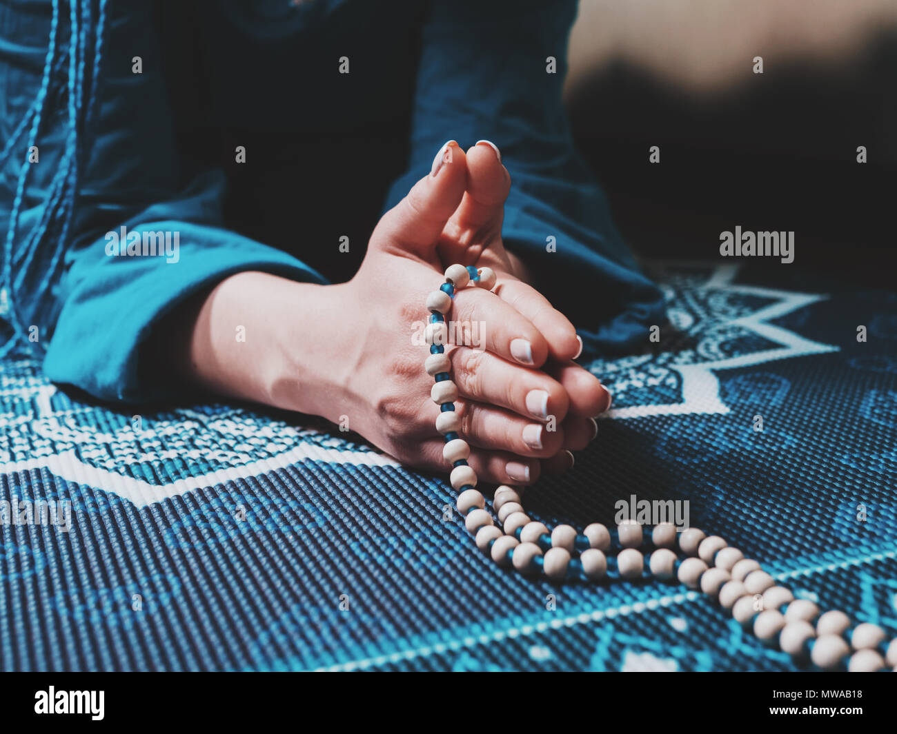 Concentrated Woman Praying With Wooden Rosary Beads On Yoga Mat Mandala Namaste Close