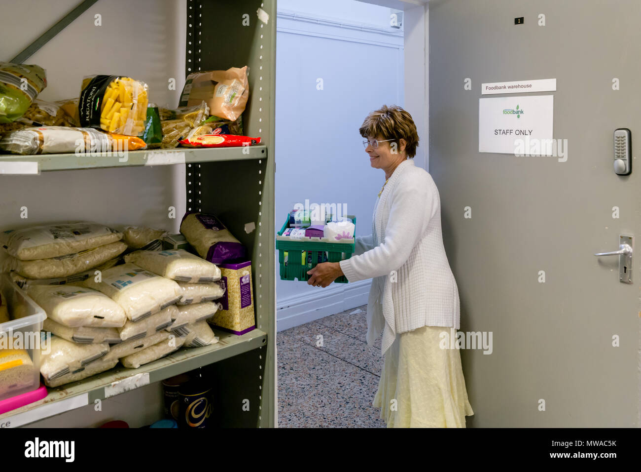 A local church food bank (part of Trussell Trust) dealing with period poverty - a female volunteer offers clients a selection of sanitary products - Stock Image