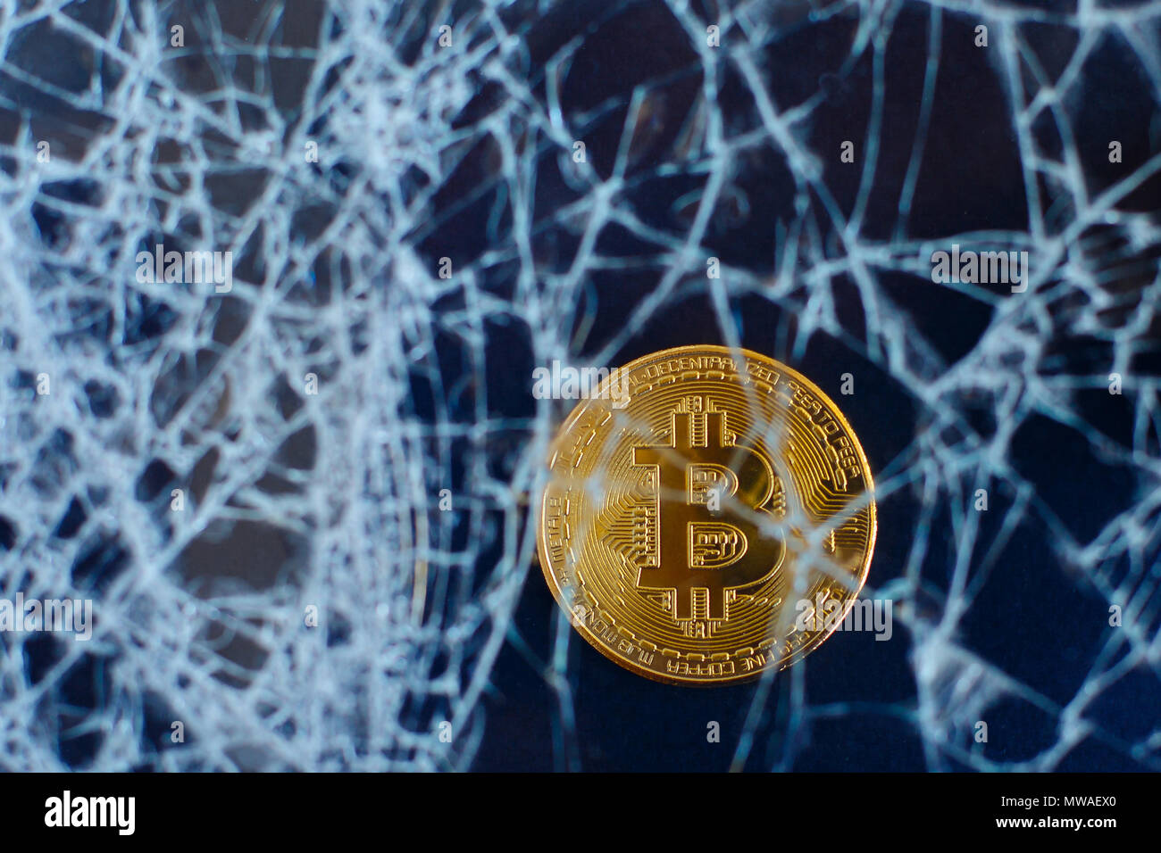 Bitcoin and cracked glass on black background. The fall of bitcoin. Crash Collapse Stock Photo
