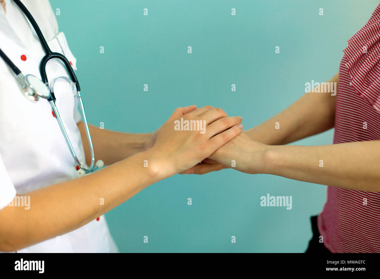 Female doctor's hands holding patient's hand for encouragement and empathy. Partnership, trust and medical ethics concept. - Stock Image