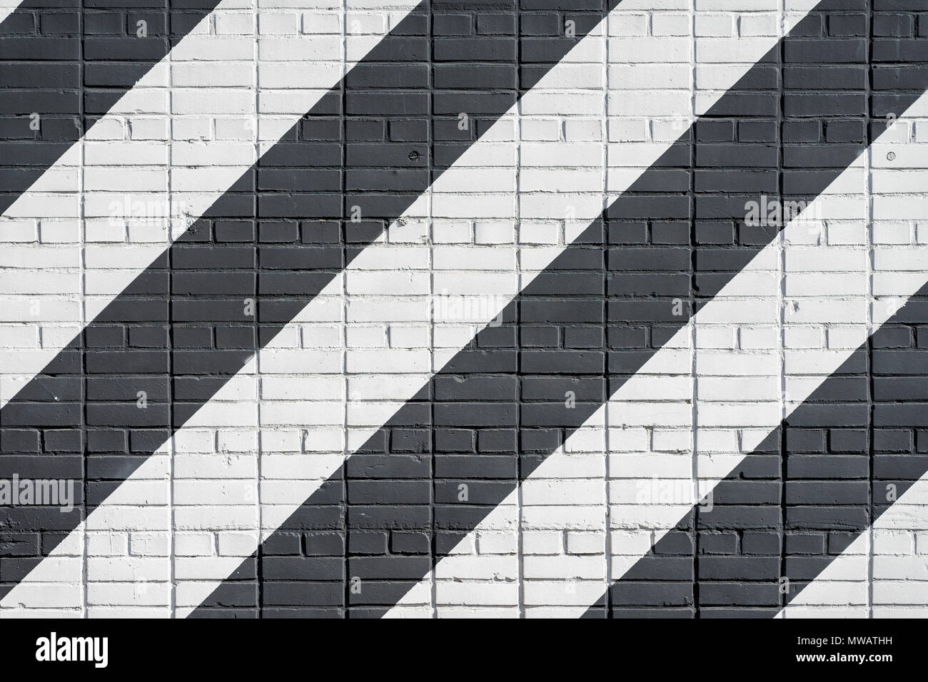 Diagonally painted bricks surface of wall in black and white color, as graffiti. Graphic grunge texture of wall. Abstract modern background - Stock Image