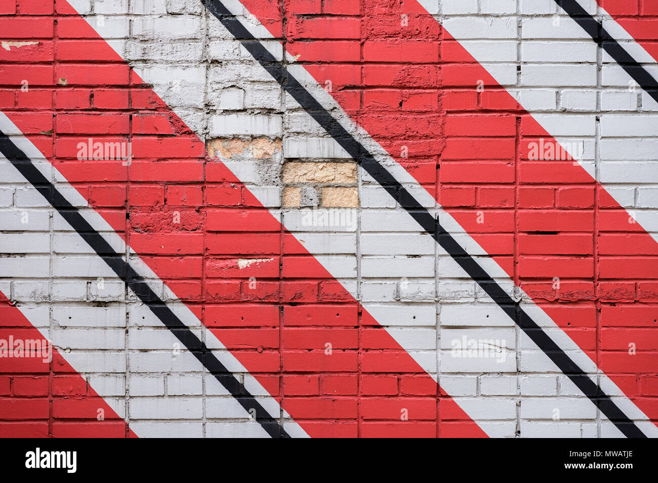 Diagonally painted bricks surface of wall in red, black and white colors, as graffiti. Graphic grunge texture of wall. Abstract geometric modern background - Stock Image