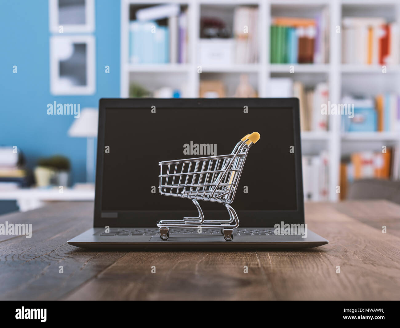 91049f2b9c9 Miniature shopping cart and laptop on a desk  online shopping and  e-commerce concept