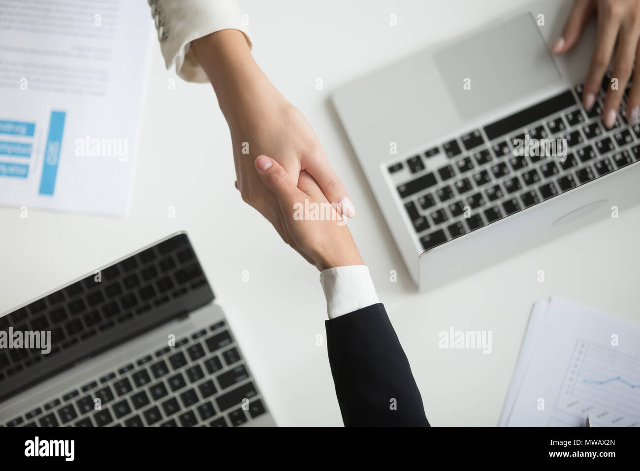 Female hands shaking at meeting making deal, top closeup view - Stock Image