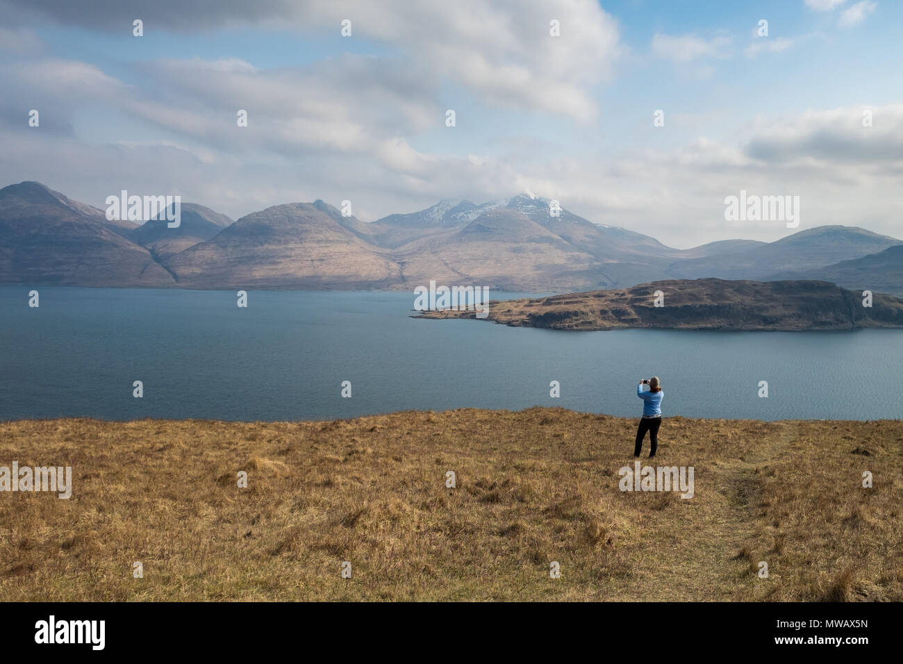 Woman taking a photo of the dramatic scenery of Ben More mountain across loch Na Kea on the Isle of Mull in Scotland - Stock Image