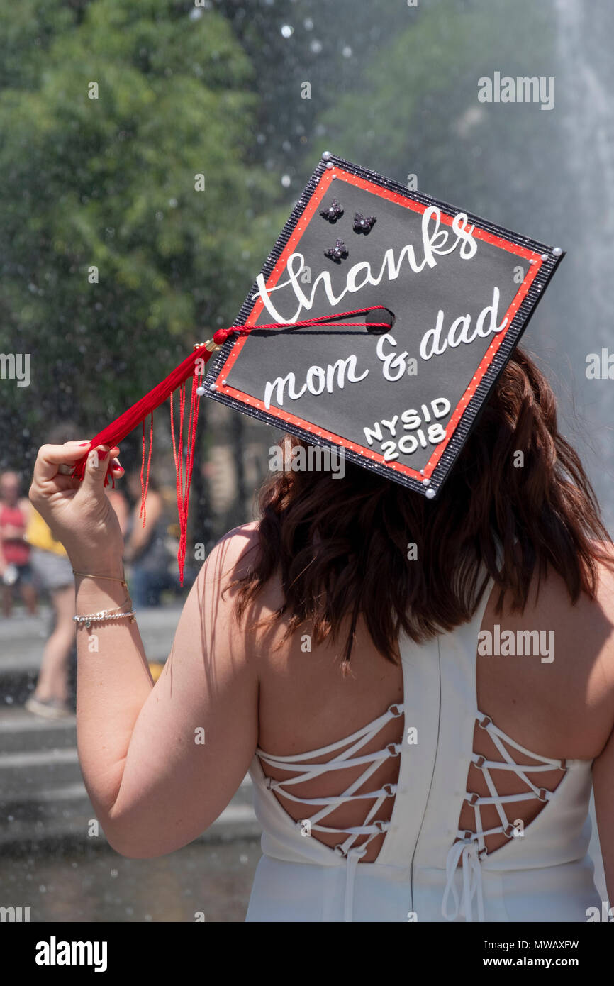 A graduate of the New York School of Interior Design with a cap thanking her father and mother. In Washington Square Park in Greenwich Village. - Stock Image