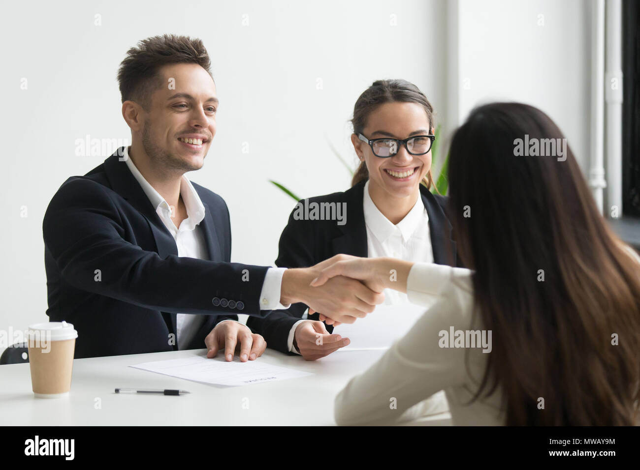 Smiling hr manager handshaking hired female applicant at job int - Stock Image