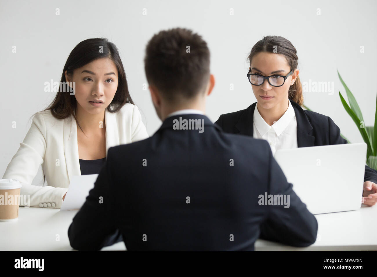 Serious unconvinced diverse hr managers interviewing male job ap - Stock Image