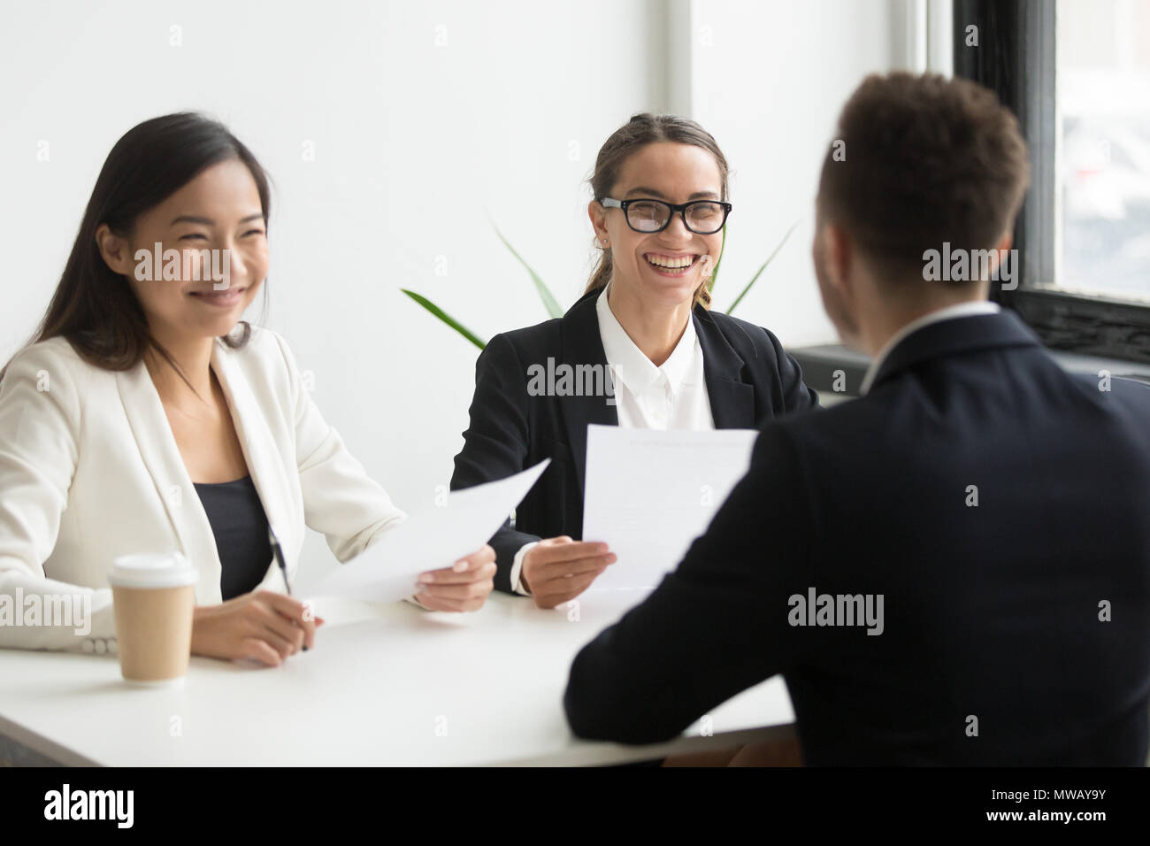 Positive hr executives laughing at job interview with successful - Stock Image