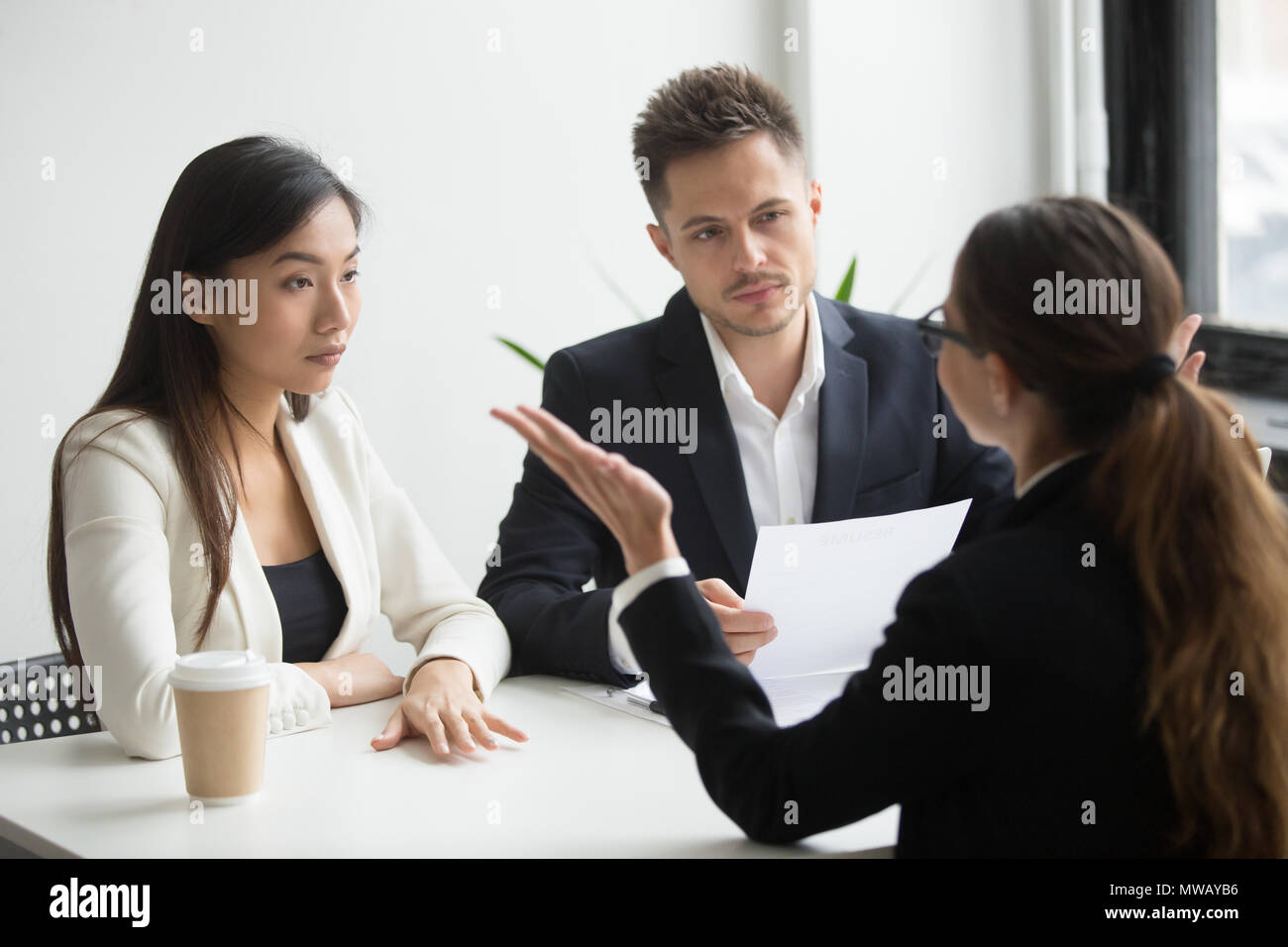 Skeptical diverse hr managers interviewing female applicant, bad - Stock Image